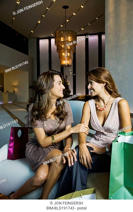 Smiling Hispanic women surrounded by shopping bags