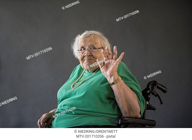 Portrait of senior woman sitting in wheelchair and waving hand
