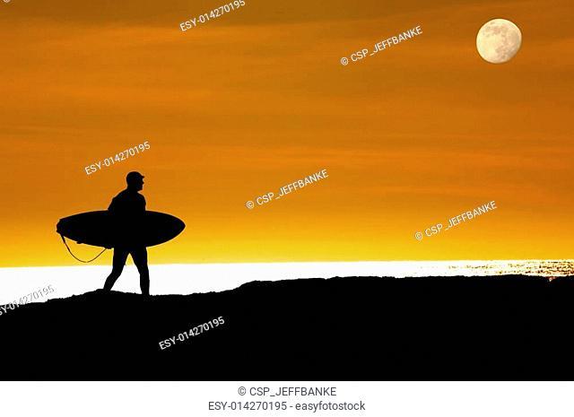 Surfer walking on cliffs to last ride