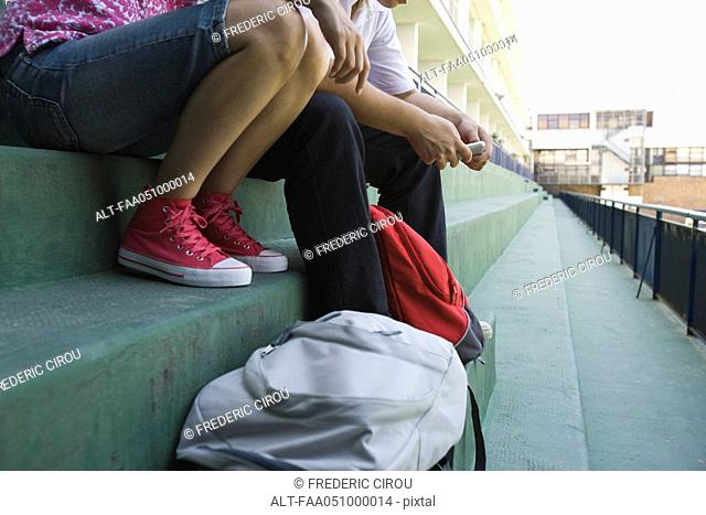 Teenagers sitting together on steps, low section