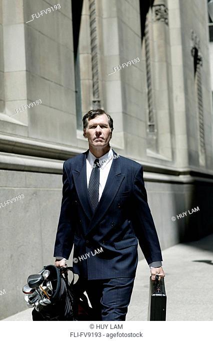 Businessman Carrying Golf Clubs, Toronto, Ontario