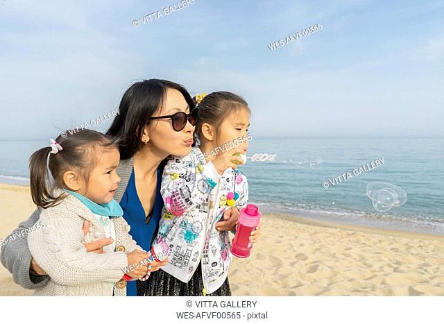 Mother with two daughters blowing soap bubbles on the beach