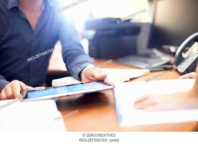 Man at desk with digital tablet in a library