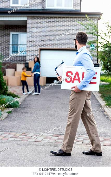 realtor with sale sign walking in front of people moving into new house