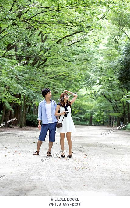 A couple, a man and woman in a Kyoto park in an avenue of mature trees