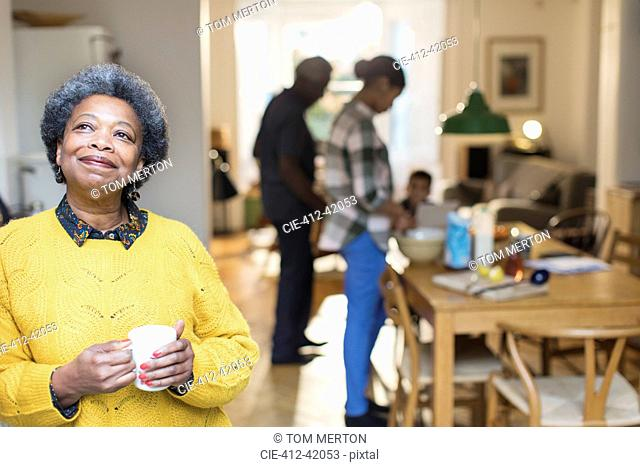 Smiling, satisfied senior woman drinking coffee with family in background