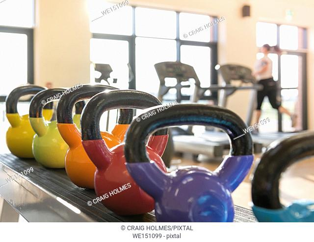 Kettle weights in a gym with a woman on a treadmill in a gym