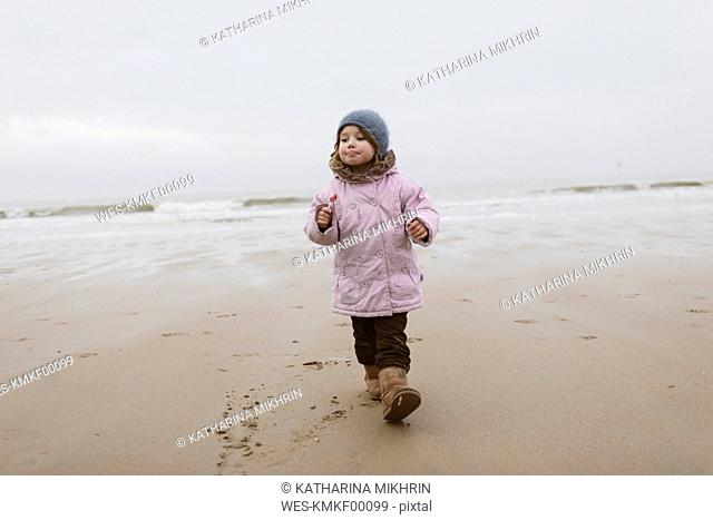 Germany, North Sea Coast, little girl with lolly strolling on the beach in winter