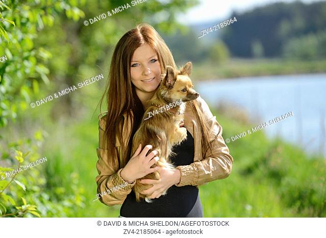 Close-up of a young woman with her Chihuahua dog in spring