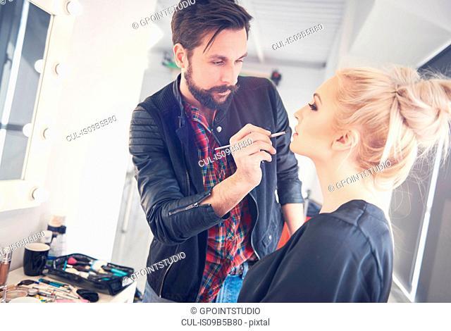 Male make up artist applying lipstick to model for photo shoot