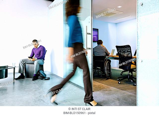 Blurred view of businesswoman walking in office