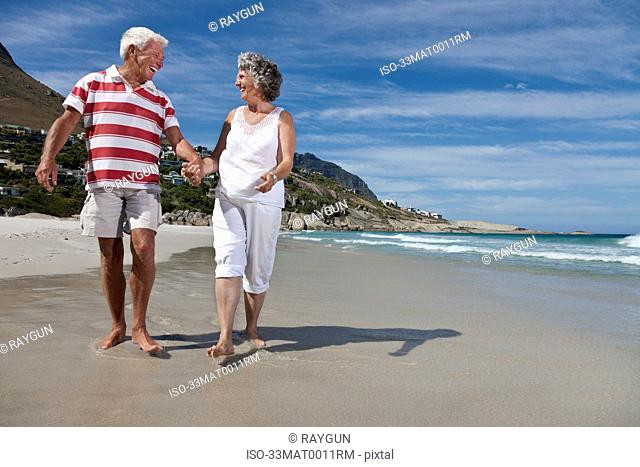 Older couple walking together on beach