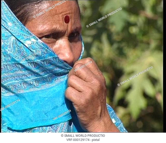 Woman in traditional dress hiding her face. Nepal