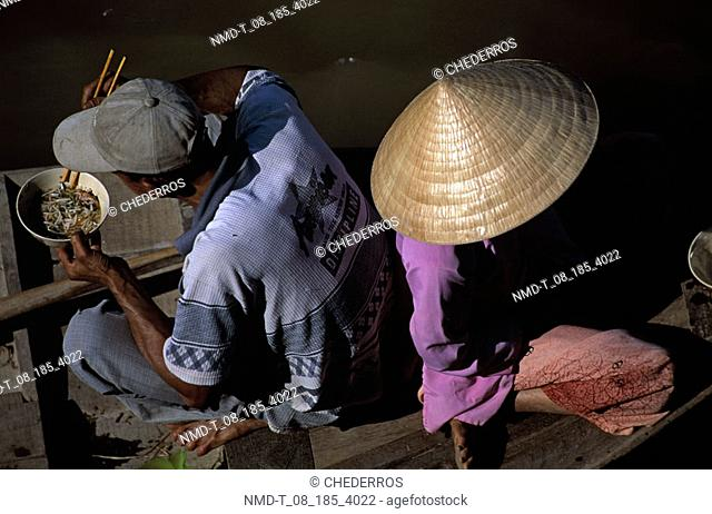 High angle view of a mid adult man with a mid adult woman on a boat, Vietnam