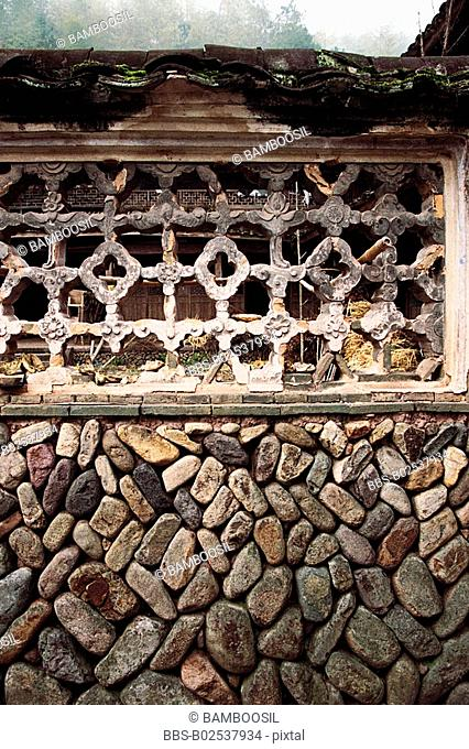 View of a window with latticework on a stonewall, Paper-cut for Decoration of Window in Stone Wall of Ancient House, Taishun County, Zhejiang Province