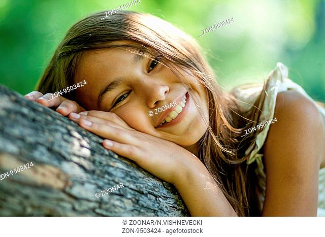 Happy young girl sitting in a tree