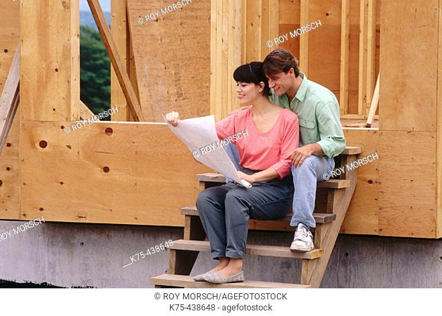 Couple looking at blueprints of new home
