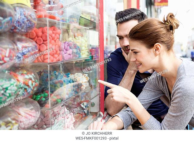 France, Paris, couple looking at sweets in a window display