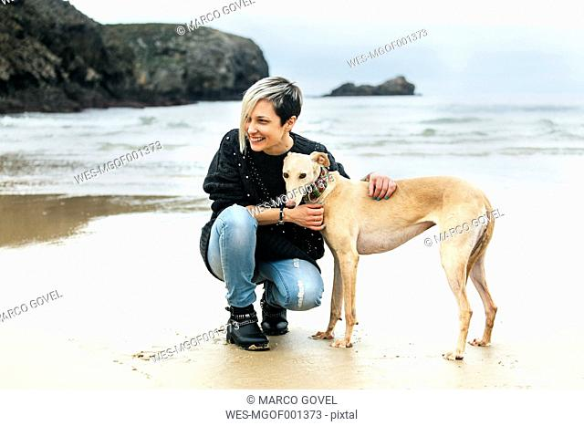 Spain, Llanes, happy young woman with her greyhound on the beach