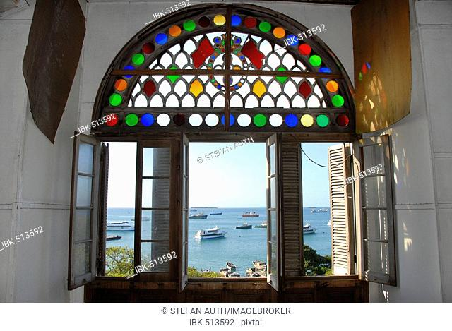View through colourful open window of Beit el-Sahel Palace Museum to the sea with ships Stone Town Zanzibar Tanzania