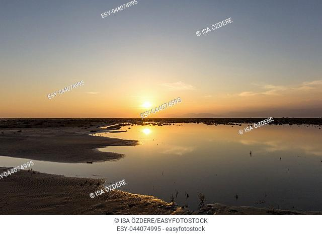 Golden natural small lake or pond sunset view of blue and orange sky landscape. Sunset or sunrise reflection in nature with sun in clouds above small water lake...
