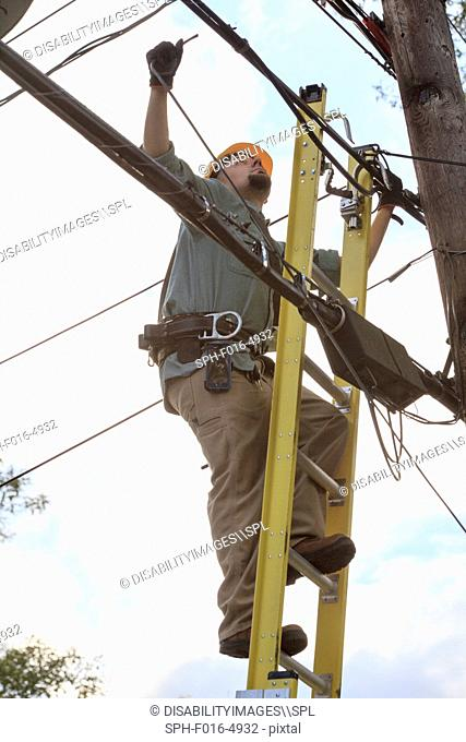 Lineman attaching cable at power pole