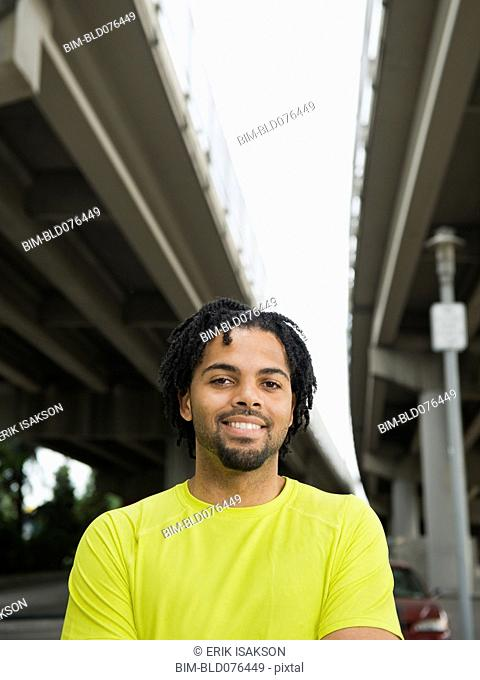Mixed race man smiling under freeway overpass