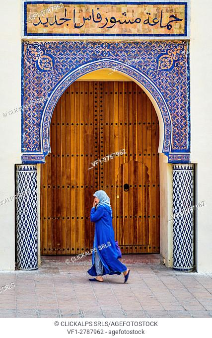 Fes, Marocco, North Africa. Woman with blue traditional dress in front of a typical moroccan door