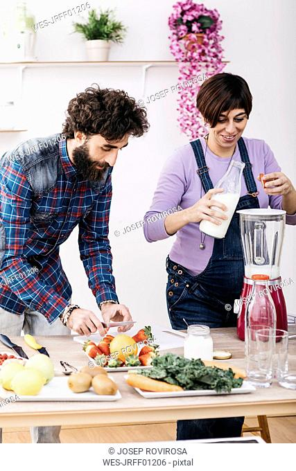 Couple preparing smoothies with fresh fruits and vegetables
