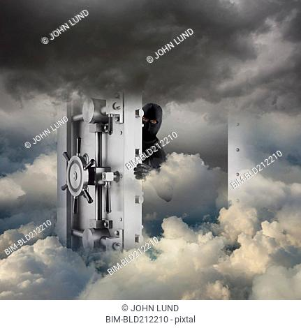 Caucasian robber opening bank vault in clouds