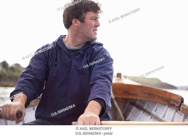 Portrait of man rowing in boat, Wales, UK