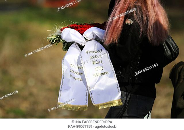 Awoman carries a wreath reading 'Unsere Herzen trauern' (lit. 'Our hearts mourn')and 'Freeway Riders Black City Women' at the burial of nine-year-old Jaden