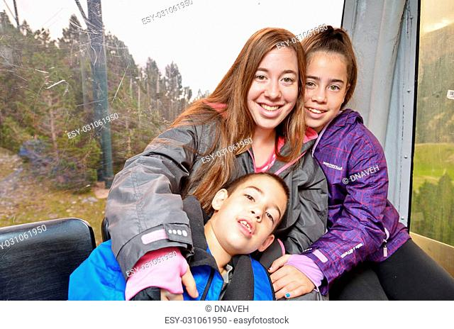 Portrait of three siblings (brother two sisters) hugging having fun in a cable car while touring the Spanish Pyrenees