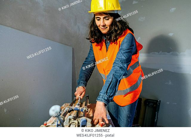 Woman on construction site cutting tiles