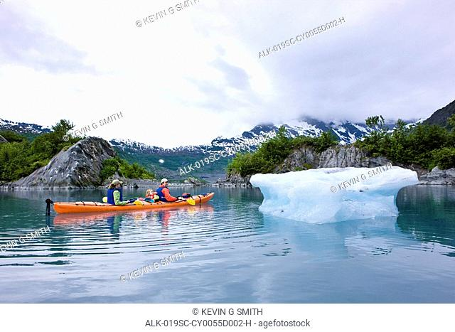 Family kayaking in Shoup Bay close to an iceberg from Shoup Glacier, Prince William Sound, Southcentral Alaska