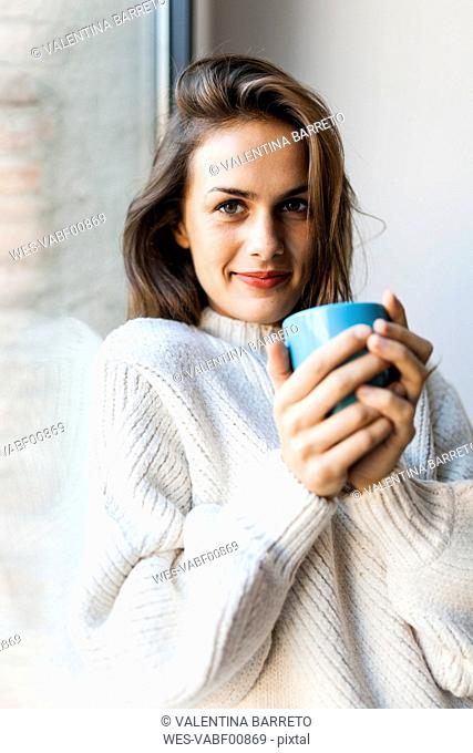 Smiling young woman drinking a coffee at a window