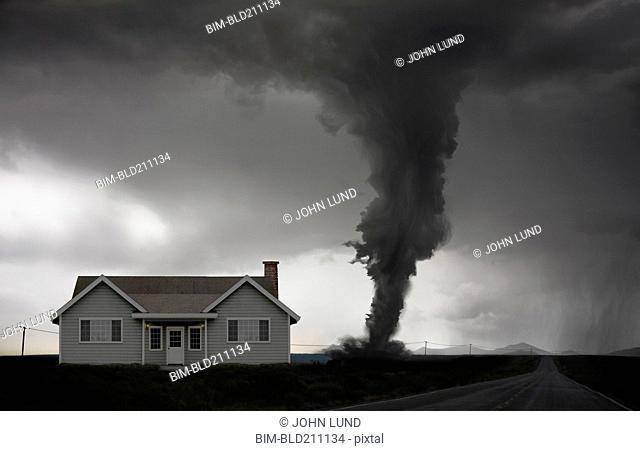 Tornado approaching house in rural landscape