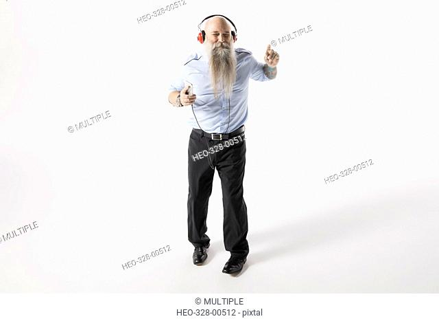 Cool hipster businessman with beard dancing, listening to music with headphones against white background