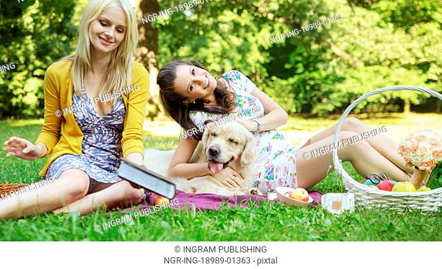 Young women playing with friendly dog