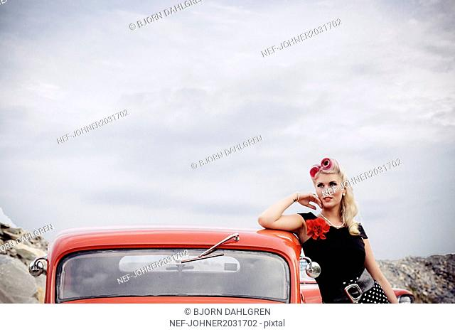 Woman wearing retro clothes near vintage car