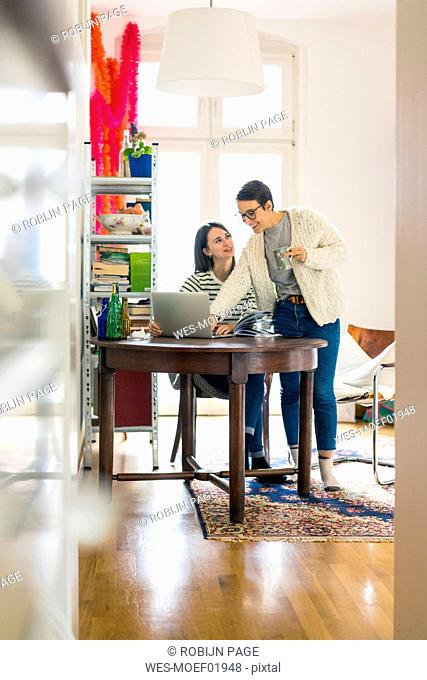 Two girlfriends at home, talking and using laptop