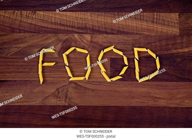 Close up of word food written with penne on wooden background