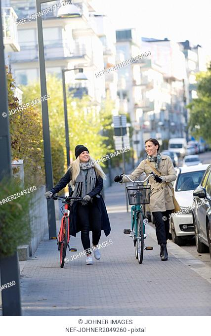 Women walking with bicycles in city