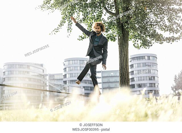 Young businessman balancing on slackline