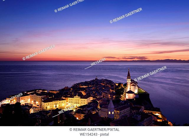 Purple Adriatic Sea after sundown with lights on Piran Slovenia Tartini Square Courthouse City Hall St Francis church and St George's Cathedral