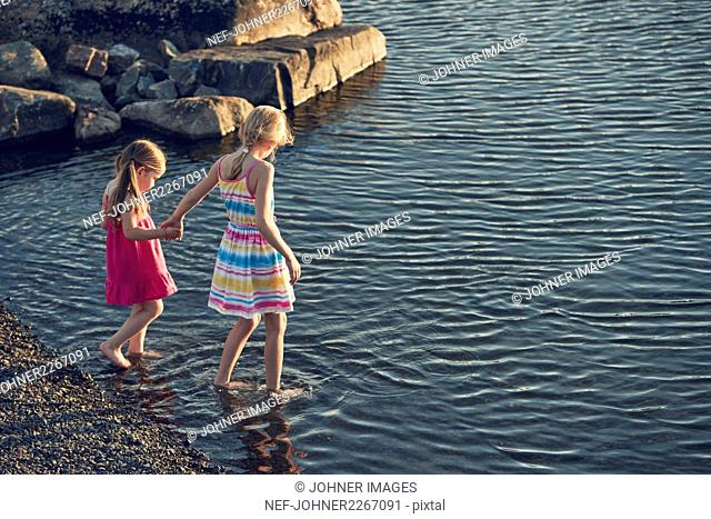 Girls wading in lake
