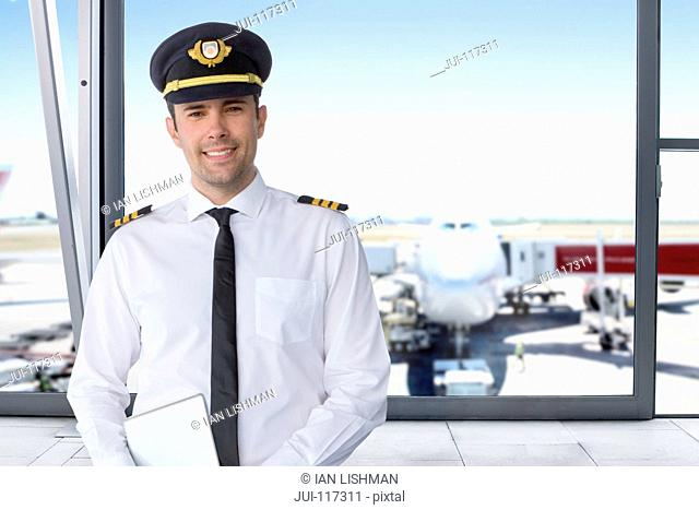 Portrait Of Airline Pilot Standing In Airport Lounge