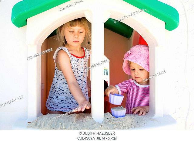 Female toddler and sister playing with sand on playhouse windowsill