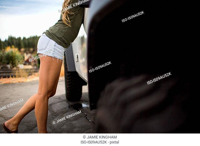 Neck down view of young woman in shorts leaning forward on jeep