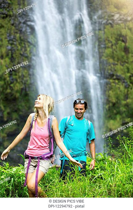 Couple having fun together outdoors on hike to amazing waterfall in Hawaii